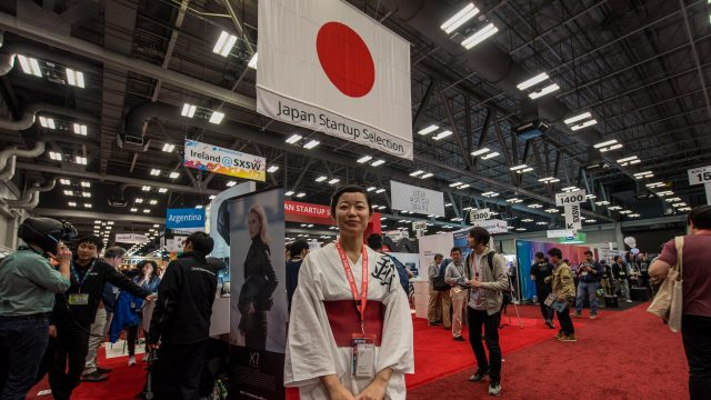 A woman from the Japanese delegation stands in the middle of the International section of the SXSW Trade Show 2017.
