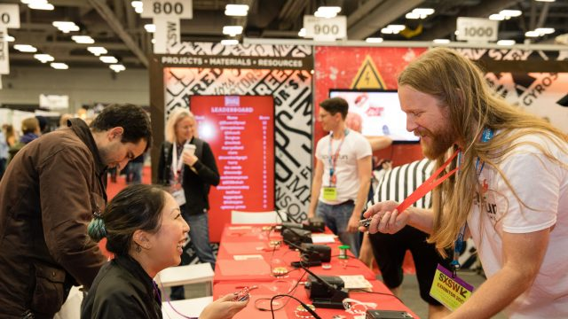 A SXSW attendee interacts with an exhibitor at the SXSW Trade Show in 2017