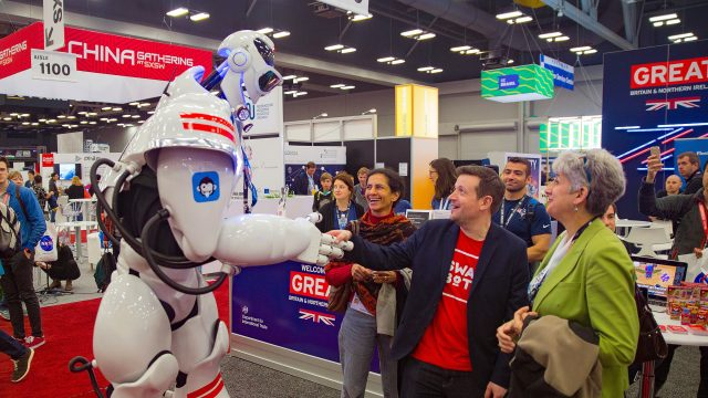 A man shakes hands with a robot at the Trade Show during SXSW 2017.