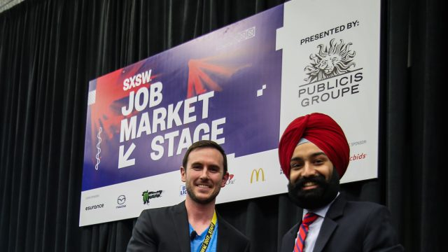 A SXSW employee congratulates the winner of one of the SXSW Job Market Live Competitions.