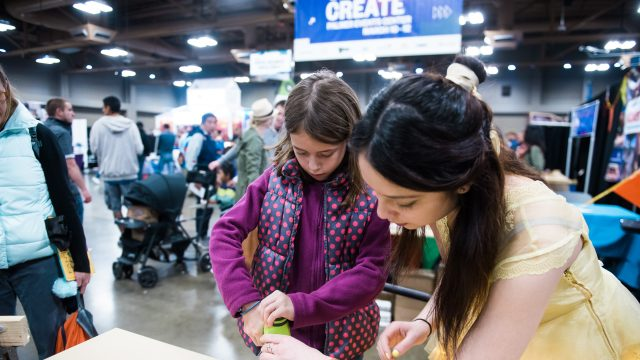 A woman shows a child how to use a drill at SXSW Create 2017