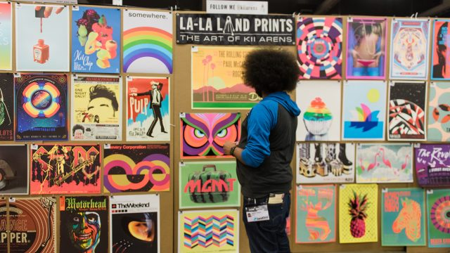 A SXSW attendee looks at poster art during Flatstock 59.