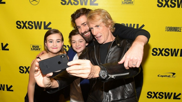 Michael Bay taking a selfie with John Krasinski, Noah Jupe, and Millicent Simmonds.