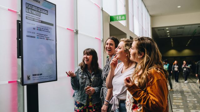 Girls looking at digital sign at SXSW 2018 - Photo by Judy Won