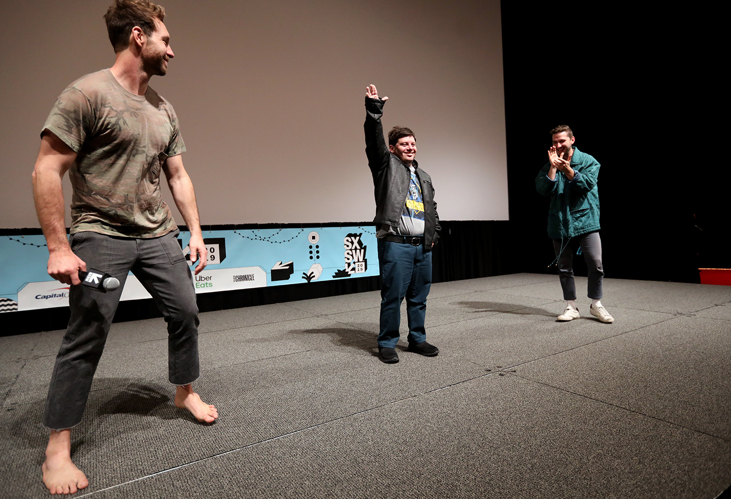(L-R) Tyler Nilson, Zack Gottsagen, and Shia LaBeouf speak onstage at The Peanut Butter Falcon Premiere at the Atom Theater.